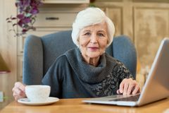 Smiling Senior Woman Using Laptop. Portrait of elegant senior woman using laptop and  looking at camera while working in modern cafe Royalty Free Stock Images