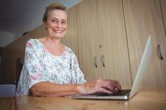 Smiling senior woman using a laptop Stock Photos