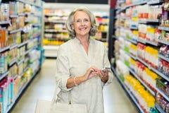 Smiling senior woman using smartphone Stock Photography