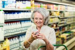 Smiling senior woman using smartphone Stock Image
