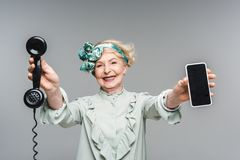 Smiling senior woman with vintage phone and smartphone in hands. Isolated on grey royalty free stock image