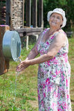 Smiling senior woman washing her hands outdoor Royalty Free Stock Photos