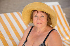 Smiling Senior woman wearing hat at beach on sunbed Stock Photos