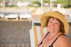 Smiling Senior woman wearing hat at beach on sunbed Stock Photo