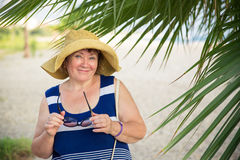 Smiling Senior woman wearing hat under the palm trees. Smiling Senior woman under the palm trees Stock Photography