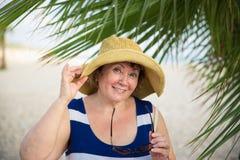 Smiling Senior woman wearing hat under the palm trees. Smiling Senior woman under the palm trees Stock Image
