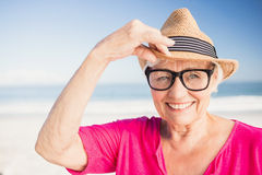 Smiling senior woman wearing straw hat. On the beach Stock Photo