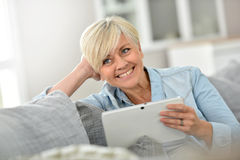Smiling senior woman websurfing on tablet Royalty Free Stock Photos
