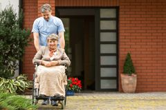 Senior woman in the wheelchair supported by caregiver in front of house stock image