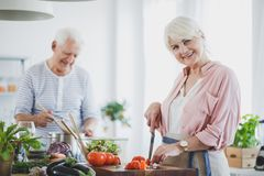 Smiling senior woman cutting tomatoes Stock Photo