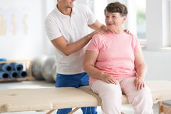 Physiotherapist massaging smiling senior woman Stock Photo