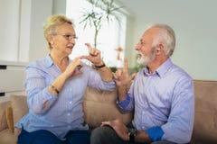 Senior woman talking using sign language with her hearing impairment man stock photo