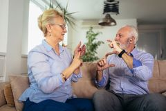 Senior woman talking using sign language with her hearing impairment man. Smiling senior women talking using sign language with her hearing impairment man stock photos