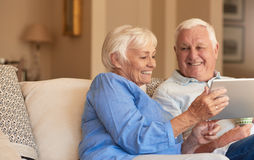Smiling seniors browsing the internet from their living room sofa. Content senior couple talking and relaxing together while sitting on a sofa in their living Royalty Free Stock Photos