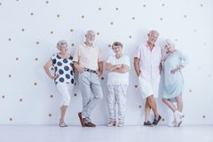 Smiling seniors in casual clothes. Against white wallpaper with gold dots royalty free stock images