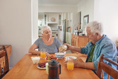 Smiling seniors enjoying a healthy breakfast at home together. Content senior couple smiling and talking together while sitting at their dining table in the Stock Photos