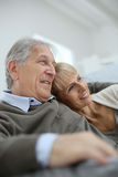 Smiling seniors relaxing in sofa looking towards future Stock Photo