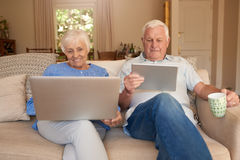 Smiling seniors sitting on their sofa browsing the internet. Content senior couple using a laptop and digital tablet while sitting happily together on their Royalty Free Stock Photo