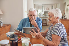 Smiling seniors talking and using digital tablets together over breakfast Stock Photography