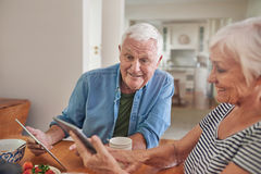 Smiling seniors using digital tablets together over breakfast Royalty Free Stock Image