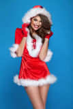 Smiling sensual santa claus. Smiling happy brunette woman wearing santa claus costume posing, looking at camera royalty free stock image