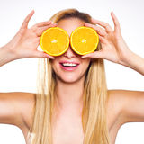 Smiling sensual woman holding slices of oranges to her eyes. Royalty Free Stock Images