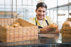 Smiling server in apron holding bread Royalty Free Stock Images
