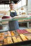 Smiling server standing with arms crossed behind the counter. At the bakery Stock Photography