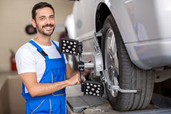 Smiling  serviceman checking wheel Royalty Free Stock Photos