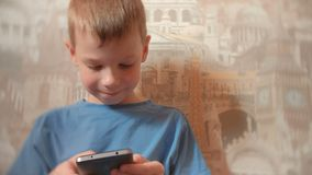 Smiling seven-year-old boy playing games on his mobile phone. Smiling seven-year-old boy playing games on his mobile phone stock footage