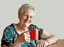 Smiling seventy-something woman with mug. Beautiful elderly lady enjoying a cuppa against plain background Stock Image