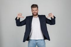 A smiling sexy bearded man with a beautiful hairdo points his fingers on his t-shirt. place for your text or logo. dressed in a stock photos