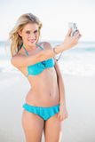 Smiling blonde in bikini taking a self picture Royalty Free Stock Photos