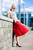 Smiling blonde girl wearing red skirt Royalty Free Stock Images