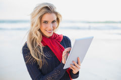 Smiling sexy blonde holding tablet computer Stock Image