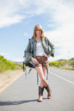 Smiling sexy blonde posing while hitchhiking. On a deserted road in summertime Royalty Free Stock Images