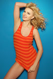 Smiling sexy blonde woman in orange top Stock Images