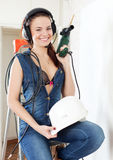 Smiling  girl in headphones with drill and hardhat Stock Photo