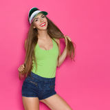 Smiling And Sexy. Smiling sexy girl in lime green shirt, green sun visor and jeans shorts holding her long hair and looking at camera. Three quarter length Royalty Free Stock Image