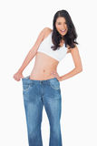 Smiling sexy woman wearing too big jeans Stock Photo