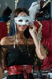 Smiling woman with white carnival mask with feather. stock image
