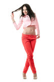 Smiling sexy young brunette in red jeans Stock Photography