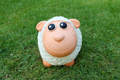 Smiling sheep doll on the grass Stock Photos