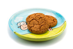 Smiling sheep underneath cookies on a colorful plate Royalty Free Stock Photo