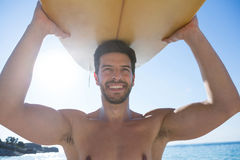 Smiling shirtless man carrying surfboard at beach. On sunny day Royalty Free Stock Photography