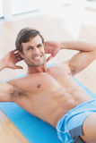 Smiling shirtless man doing sit ups in fitness studio Stock Image