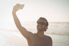 Smiling shirtless man taking selfie at beach Stock Image