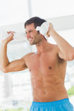 Smiling shirtless man with towel in gym Stock Photography
