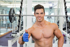 Smiling shirtless muscular man giving thumbs up in gym Stock Images