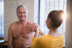 Smiling shirtless senior male patient looking at female therapist giving arm massage. At hospital ward Royalty Free Stock Photo